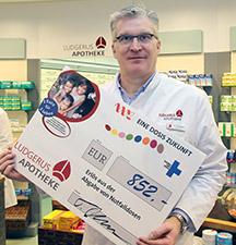 Apotheker Thorsten Gottwald überreicht einen Spendenschekc