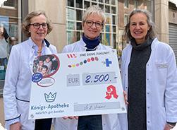 Apothekerin Masur und zwei Kolleginnen übergeben den symbolischen Scheck über 2.500 Euro