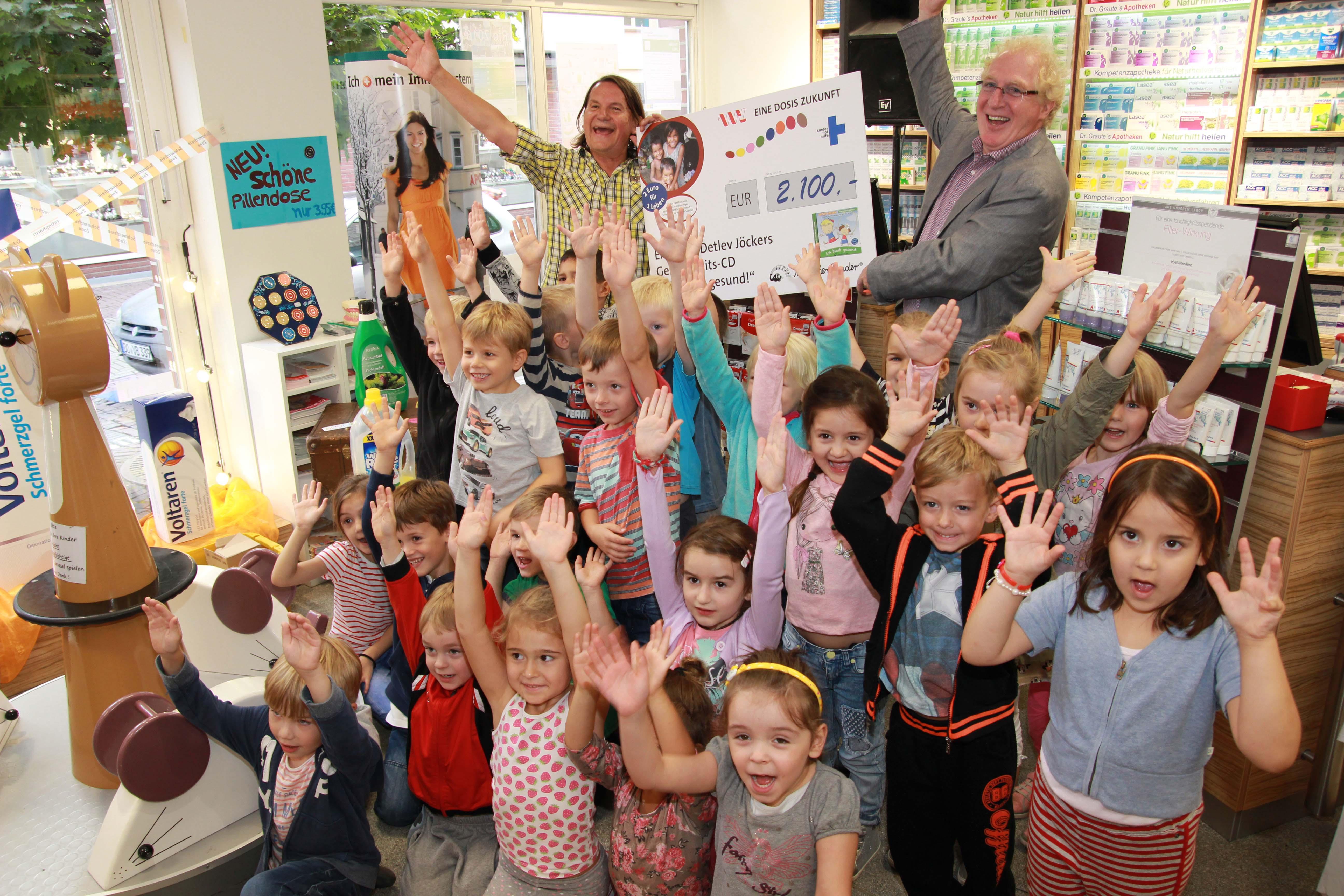 Detlev Jöcker (links) überreichte einen Spendenscheck an Dr. Wolfgang Graute, Vorstandsmitglied der Apothekerkammer Westfalen-Lippe - umringt von den Kids des Overberg-Kindergartens.